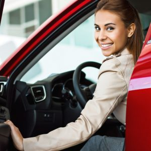 Photo of happy young mixed race woman sitting inside her new car. Concept for car rental