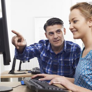 Man Training Woman On Computer In Office