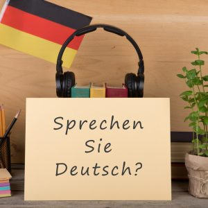"Learning languages concept - paper with text ""sprechen sie deutsch?"", flag of the Germany, books, headphones, pencils on wooden background"