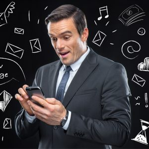 Businessman using smartphone and chalkboard business icons around