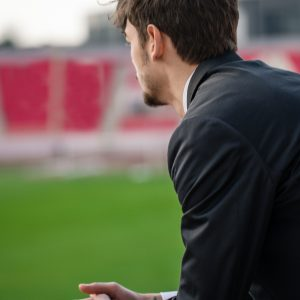 Well dressed young businessman coach, coaching his team on a stadium.